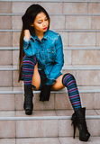Fashionable pretty young woman wearing striped knee socks, sitti Stock Images