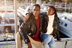Fashionable professional couple of models posing outdoors. Portrait of fashionable professional couple of models posing outdoors, embracing black couple enjoying Stock Photos