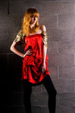 Fashionable red-haired woman in a satin red dress Royalty Free Stock Photo