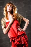 Fashionable red-haired woman in a satin red dress Royalty Free Stock Image