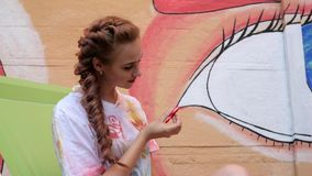 Fashionable relaxing toy in arms of girl on background of graffiti, Beautiful young woman played by spinner on street,. Modern toy for stress relief Rotates on stock video