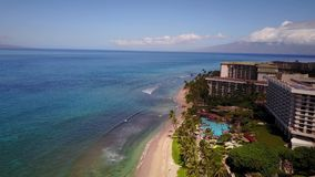 Fly over luxurious resort hyatt ,beautiful nature and pacific ocean on the background of blue sky on island maui,hawaii. Fashionable resort hyatt on the ocean stock video footage