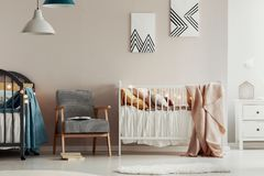 Retro armchair between two wooden cribs in cute twins nursery royalty free stock photo