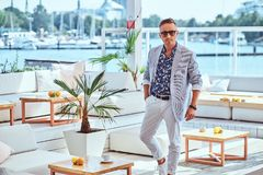 Fashionable rich man with stylish hair dressed in modern elegant clothes at the outdoor restaurant against the. Fashionable rich man with stylish hair dressed in royalty free stock photography