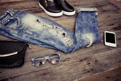 Fashionable ripped jeans, sunglasses, bag and footwear on a wood Royalty Free Stock Photography