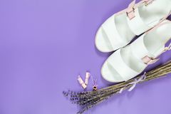 Fashionable sandals and Beautiful dried lavender bouquet on viol. Et surface. Top view, copy space. Nice holiday wedding valentin birthday card Royalty Free Stock Photography