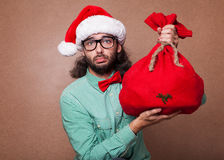 Fashionable Santa Claus derided holding a bag with gifts Royalty Free Stock Images