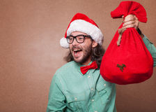 Fashionable Santa Claus derided holding a bag with gifts Stock Images