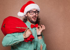 Fashionable Santa Claus derided holding a bag with gifts Royalty Free Stock Photos