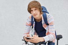 Fashionable schoolboy holding backpack wearing shirt using cell phone surfing social networks communicating with his friends leani. Ng on his bicycle. Stylish Royalty Free Stock Photos