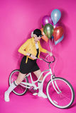 Fashionable senior woman wearing yellow leather jacket holding colorful balloons and riding bicycle. Isolated on pink Stock Image