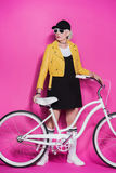 Fashionable senior woman wearing yellow leather jacket standing with bicycle Royalty Free Stock Images