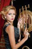 Fashionable sensual attractive lady with  black dress  standing near a safe in a vintage scene. Short hair blonde woman Stock Images