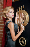 Fashionable sensual attractive lady with  black dress  standing near a safe in a vintage scene. Short hair blonde woman Royalty Free Stock Photography