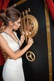 Fashionable sensual attractive lady with white dress standing near a safe in a vintage scene. Short hair brunette woman royalty free stock photo