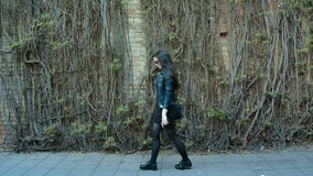 Fashionable Sexy brunette in black clothing walking down the street stock video