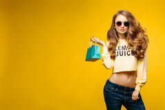 Fashionable sexy brunette in sunglasses posing with little blue bag. Stock Photos