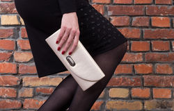 Fashionable sexy woman posing in elegant fitting dress. With  leather clutch in hands Royalty Free Stock Images