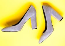 Fashionable shoes concept. Shoes made out of grey suede on yellow background. Pair of fashionable high heeled shoes. Footwear for women with thick high heels Stock Photos
