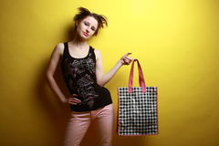 Fashionable shopping. Young defiant girl with paper-bag, isolated on yellow Stock Image