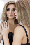 Fashionable shot of a sexy beautiful girl in mirrors in black clothes with makeup smokey eyes Royalty Free Stock Photos