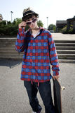 Fashionable skateboarder standing in parking lot Royalty Free Stock Images