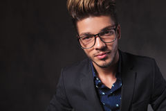 Fashionable smart man wearing glasses in dark studio Royalty Free Stock Images