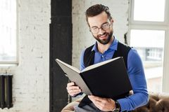 fashionable smiling businessman reading notebook in loft royalty free stock images