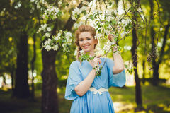 Fashionable smiling girl near blossom tree Stock Photo