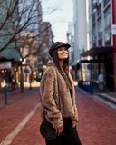 Fashionable smiling young female carrying sling bag standing on stock images