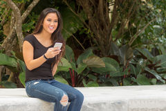 Fashionable smiling young pretty Asian woman texting on smart ph Royalty Free Stock Photography