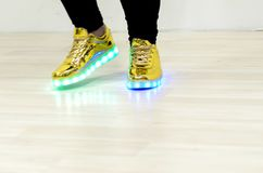 Fashionable sneakers with LED lighting on the legs of a girl royalty free stock image