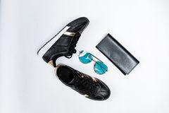 Fashionable sneakers on a white sole with black socks and gold accents, sunglasses with blue glasses and a black purse on a white royalty free stock image
