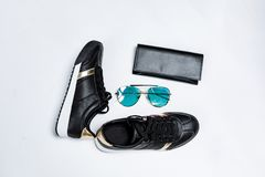 Fashionable sneakers on a white sole with black socks and gold accents, sunglasses with blue glasses and a black purse on a white stock photo