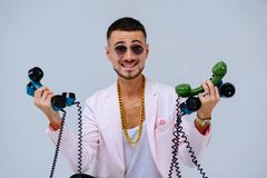 Fashionable sophisticated man in a pink jacket and black pants, with a lot of handsets, a manifestation of emotions surprise screa. M irritability, hand gestures royalty free stock images