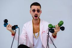 Fashionable sophisticated man in a pink jacket and black pants, with a lot of handsets, a manifestation of emotions surprise screa. M irritability, hand gestures royalty free stock image