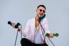 Fashionable sophisticated man in a pink jacket and black trousers, with a lot of handsets, the expression of emotions gestures han. Ds space for text stock photos