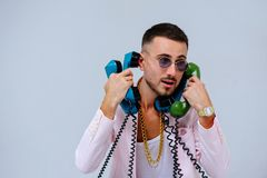 Fashionable sophisticated man in a pink jacket and black trousers, with a lot of handsets, the expression of emotions gestures han. Ds space for text stock image