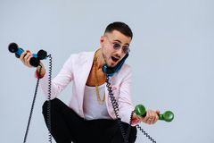 Fashionable sophisticated man in a pink jacket and black trousers, with a lot of handsets, the expression of emotions gestures han. Ds space for text royalty free stock photos