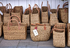 Fashionable straw shopping bags at market. Straw shopping bags exposed at open air market on summer Stock Photography
