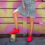 Fashionable street style female outfit with red sport sneakers and casual dress. Royalty Free Stock Photo
