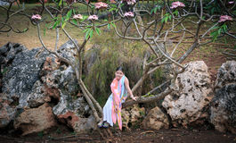 Fashionable styled little girl sitting on tropical tree surrounded by a big natural rocks Stock Images