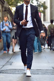 Fashionable stylish businessman walking on city street and texting on the cell phone. Stock Photos