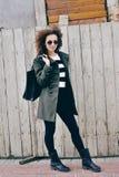 Fashionable stylish girl with bag and jacket wearing sunglasses. Stock Photography