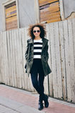 Fashionable stylish girl with bag and jacket wearing sunglasses. Royalty Free Stock Images