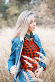 Fashionable stylish girl in a denim dress and a red checkered sh Royalty Free Stock Photos