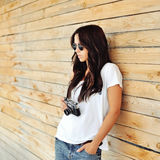 Fashionable stylish girl with old camera wearing sunglasses and Stock Images
