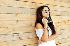 Fashionable stylish girl with old camera wearing sunglasses and Royalty Free Stock Photos