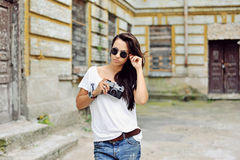 Fashionable stylish girl with old camera wearing sunglasses and Stock Photo
