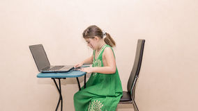 Fashionable stylish little girl sitting behind a table and doing her computer home work Stock Image